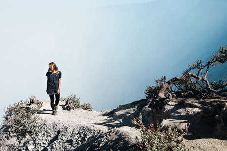 Young woman in protective mask on summit of active volcano Kawah Ijen above crater acid lake with poisonous fume. Popular travel destination, adventure hike on family vacation in Bali, Java, Indonesia