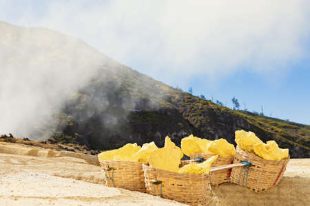 Heavy basket laden by pieces of natural sulfur to carry by miners from crater mine. Manual labour intensive sulphur mining operation in Kawah Ijen volcano. Popular travel destination in Java Indonesia