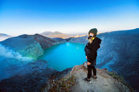 At sunrise girl stand on rock above volcano Kawah Ijen crater. Look at largest in world acid lake, sulphur mine. Popular travel destination, adventure hike on family vacation in Bali, Java, Indonesia