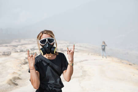 Young women in protective mask walking by wastelands around Kawah Ijen volcano crater. Post apocalypse landscape with clouds of toxic gases from volcanic emissions and dead land poisoned by sulphur.