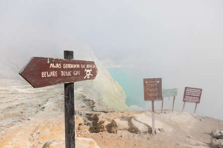 Warning signboard at wastelands in Kawah Ijen volcano crater at sulfur mine. Post apocalypse landscape with clouds of toxic gases from volcanic emissions, acid lake and dead land poisoned by sulphur.