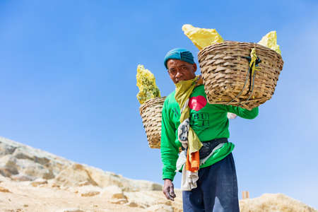 Java island, Indonesia - September 16, 2019: Basket with pieces of natural sulfur carrying on miner shoulders from crater mine Manual labour intensive at sulphur mining operation in Kawah Ijen volcano