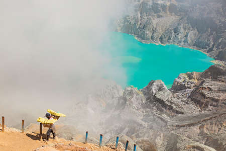 Java island, Indonesia - September 16, 2019: Basket with pieces of natural sulfur carrying on miner shoulders from crater mine. Manual labour intensive at sulphur mining operation in Kawah Ijen volcano