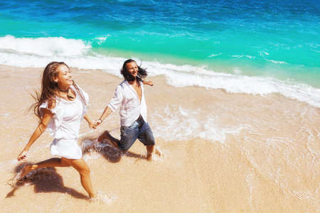 Happy family on honeymoon holiday - just married young couple having fun, run by water edge along sea beach surf. Active lifestyle, people recreational activity on summer vacation on tropical island.