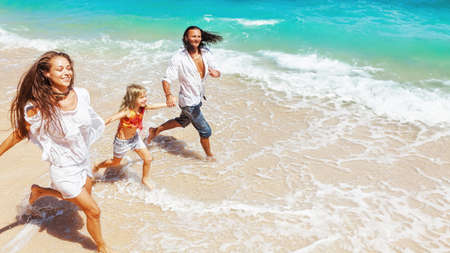 Happy family - young father, mother, baby girl hold hands, run together, child jump with fun by water pool along sea surf on tropical beach. Travel lifestyle, people walk with kid on summer vacation.