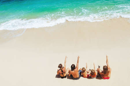 On sunny beach happy kids with parents have fun, sit on white sand see at sea surf with foam and splashes. Top view. Active children lifestyle, summer family vacation travel on tropical family resort. Banco de Imagens