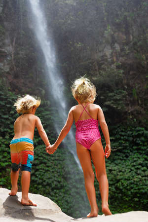 In tropical jungle happy sibling stand under waterfall, explore rainforest nature. Kids travel adventure, hiking activity with child. Lifestyle on family summer vacation and weekend walking tour.
