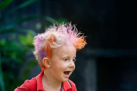 Divertido retrato de niño con peinado desordenado. Niño loco inconformista. Chico elegante con cabello pintado de colores. Niños felices divirtiéndose y celebrando en la fiesta en el campamento de verano familiar. positivo y alegre. Foto de archivo
