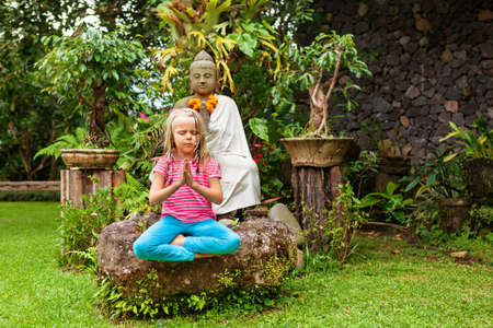 Morning funny meditation in tropical garden. Happy girl sit, relax in yoga lotus pose with mudra namaste hands. Active child healthy lifestyle, travel, summer vacation with kids at family sport camp.
