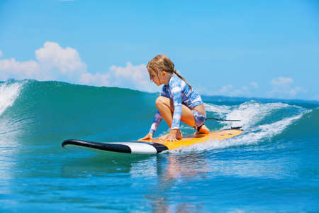 Happy baby girl - young surfer ride on surfboard with fun on sea waves. Active family lifestyle, kids outdoor water sport lessons and swimming activity in surf camp. Beach summer vacation with child. Standard-Bild