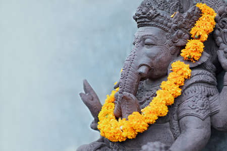 Ganesha sitting in meditating yoga pose in front of hindu temple. Decorated for religious festival by orange flowers garland, ceremonial offering. Balinese travel background. Bali island art, culture. Stock Photo - 133874309