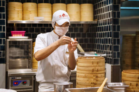 Johor, Malaysia - March 22, 2018: Asian chefs cooking traditional Chinese food in Taiwanese dumplings restaurant. Men cook and make fresh dough of steamed buns known as xiao long bao, mantou, dim sum.