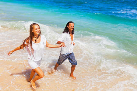 Happy family on honeymoon holiday - just married young couple having fun, run by water edge along sea beach surf. Active lifestyle, people recreational activity on summer vacation on tropical island. Stockfoto - 134260554