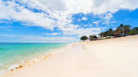 Scenic view of tropical beach with clear turquoise water and white sand. Niko beach is popular place for day tours. Nature of Bali island, best travel destinations on family vacation in Indonesia.