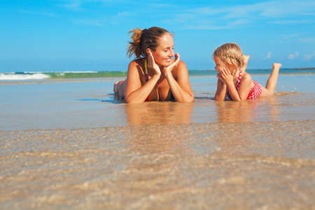 Happy people have fun in sea surf on white sand beach. Young mother with child lying in water pool. Travel lifestyle, swimming activities in family summer camp. Vacations with kids on tropical island. Stock Photo