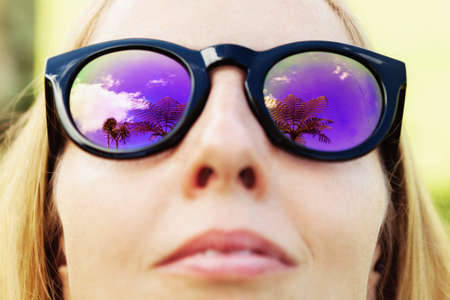 Face portrait of young happy woman wearing sunglasses and relaxing on tropical island. In mirror lenses reflecting palm trees and sky. Travel lifestyle, beach leisure on family summer vacation cruise. Banco de Imagens