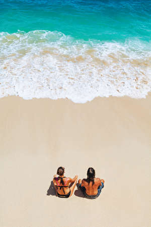 On sunny beach happy young couple relaxing, sunbathing, sit on white sand, see at sea surf with foam. Top view. Active people lifestyle, summer honeymoon vacation travel on tropical family resort.