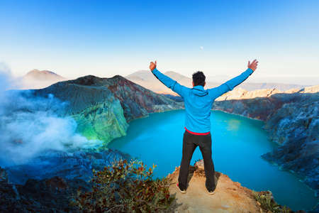 At sunrise man stand on rock above volcano Kawah Ijen crater. Look at largest in world sulphur acid lake. Popular travel destination, adventure hike, family vacations tour in Bali, Java, Indonesia
