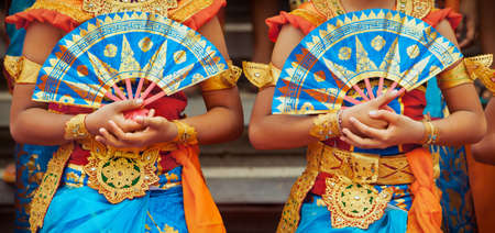 Asian travel background. Group of beautiful Balinese dancer women in traditional Sarong costumes with fans in hands dancing Legong dance. Arts, culture of Indonesian people, Bali island festivals. Фото со стока