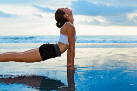 Young sporty woman stretching to keep fit at yoga retreat on sunset beach. Blue sky, ocean surf background. Travel healthy lifestyle, people outdoor activity, family summer vacation on tropical island