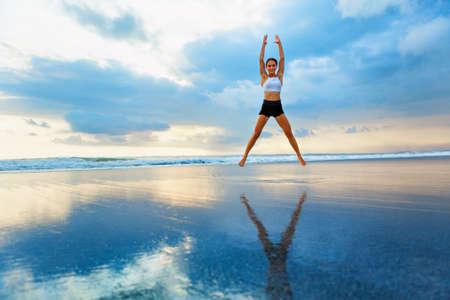 Junge Frau macht Jumping Jack oder Star Jumps Übung, um Fett zu verbrennen, fit zu bleiben. Sonnenuntergangstrand, Hintergrund des blauen Himmels. Gesunder Lebensstil im Trainingslager, Outdoor-Fitness-Aktivität, Familiensommerurlaub. Standard-Bild