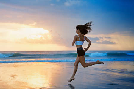Barefoot young girl with slim body running along sea surf by water pool to keep fit and burning fat. Beach background with blue sky. Woman fitness, jogging sports activity on summer family vacation.