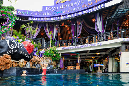 Bali, Indonesia - January 22, 2020: Natural hot spring Toya Devasya beside Batur volcano. Infinity pool with hot water and beautiful lake view. Popular travel destination on family summer holiday