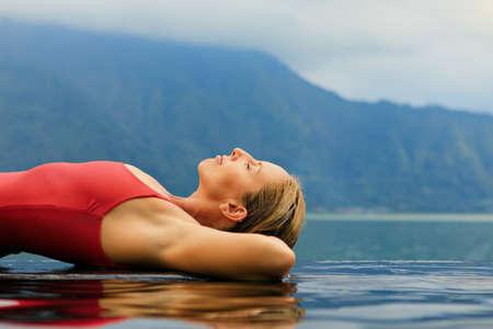 Junge Frau entspannt sich im Infinity-Pool mit Seeblick. Natürliches Thermalbad unter dem Vulkan Batur. Reise nach Kintamani, Bali. Gesunder Lebensstil, Freizeitaktivitäten im Sommerurlaub mit der Familie.