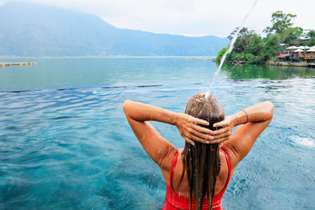 Young woman relax under flowing water in infinity pool with beautiful lake view. Natural hot spring spa beside Batur volcano. Tourist tour in Kintamani, Bali. Travel lifestyle on family summer holiday Stock Photo