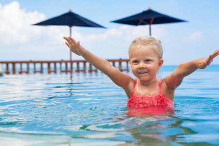 Active happy child have fun on summer beach holiday. Funny baby girl hands up in infinity swimming pool with sea view. Healthy family lifestyle, summer travel with kids on tropical islands.
