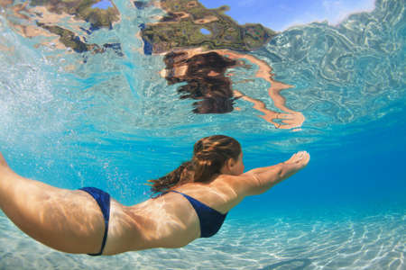Active young woman dive, swim underwater to see tropical fishes in sea lagoon pool. Swimming activity, watersports on summer beach cruise with kid. Happy family lifestyle in adventure travel camp.