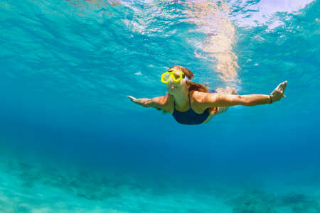 Happy family - active young woman in snorkeling mask dive, swim underwater to see tropical fishes in sea lagoon pool. Travel adventure, swimming activity, watersports on summer beach cruise with kid Stockfoto
