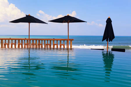 Infinity swimming pool with beach bar count, umbrellas and lounges. Beautiful view to sea surf with surfers riding on waves. Healthy lifestyle, travel background. Family summer holiday on Bali island