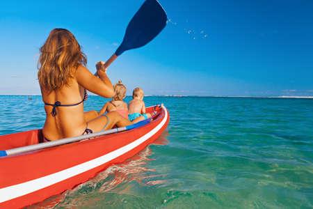 Familia feliz - madre joven, los niños se divierten en el paseo en barco. Mujer y niño remando en kayak. Estilo de vida de viaje, actividades recreativas para padres con niños, deportes acuáticos en vacaciones de verano en la playa.