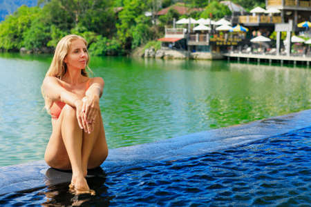 Young woman relax in infinity pool with lake view. Natural hot spring spa under Batur volcano. Travel in Kintamani, Bali. Healthy lifestyle, recreational activity on family summer holiday.