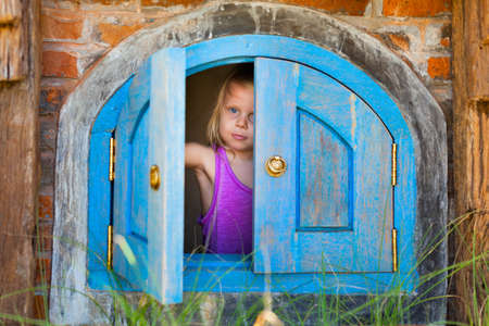 Family funny holiday. Happy baby girl peek out of toy house window in yard garden. Summer healthy lifestyle, kids outdoor activity, educational games for preschooler, recreational adventure in park. Standard-Bild