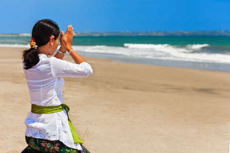 Bali island, Indonesia - March 18, 2015: Young balinese woman praying with namaste hands on sea beach at hindu ceremony before traditional religious holiday - silence day Nyepi. Éditoriale