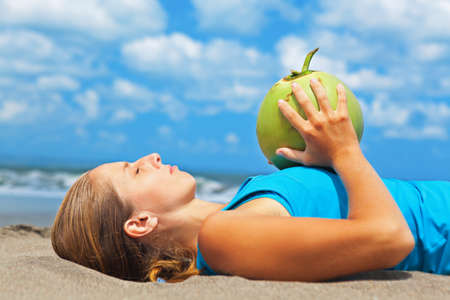 Fit woman exercising with young coconut on ocean beach. Sportive woman doing workout. Fitness woman summer vacation sport camp. Active sport lifestyle, healthy nutrition, natural diet for loss weight.