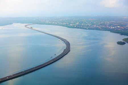Aerial view of Bali Mandara toll road over sea on Bali island. Car, motorbike bridge across the Gulf of Benoa connecting Denpasar city and South Kuta, Nusa Dua and Ngurah Rai International Airport.
