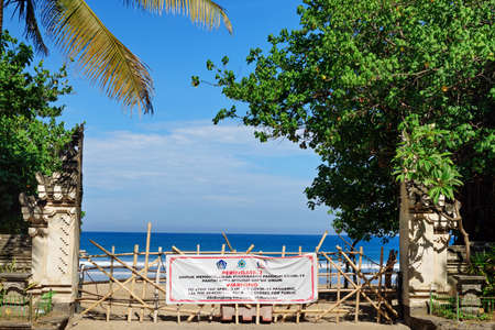 Kuta, Bali Island, Indonesia - April 16, 2020: Banner with warning sign on entrance gate to beach closed to prevent spread of coronavirus outbreak. Travel industry crisis due virus COVID-19 pandemic.