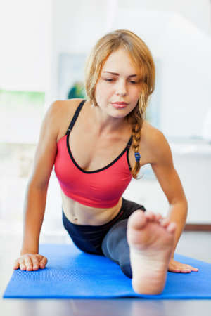 Young active woman with slim body doing stretching exercise front split to keep fit, body flexibility on yoga mat at fitness class. Sporty people training in gym, sportswear fashion, healthy lifestyle