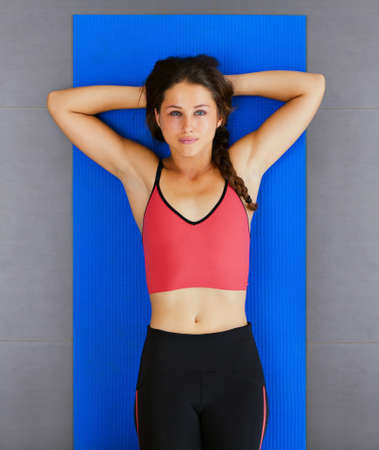 Top view of young active woman with slim body relaxing after abdominal crunches exercise on yoga mat at group fitness class. Sporty people training in gym, sportswear fashion, healthy lifestyle Foto de archivo