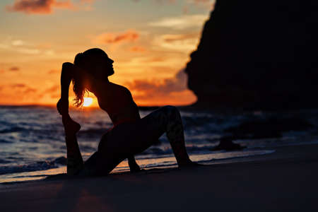 On sunset sea beach sporty young woman doing exercise, stretching to keep feet. Healthy lifestyle dark background. Outdoor sports activity at tropical island yoga spa retreat, family summer vacation.