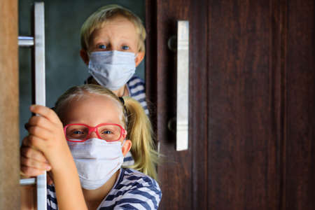 Little children looking out opened door after staying at home due banned street activity. Kids wearing medical face masks go out for outside walk. Ending coronavirus Covid-19 disease quarantine.