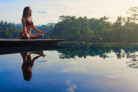 Good morning with yoga meditating on sunrise background. Active woman in bikini practicing at villa poolside to keep fit and health. Woman fitness training, sport activity on summer family holiday.