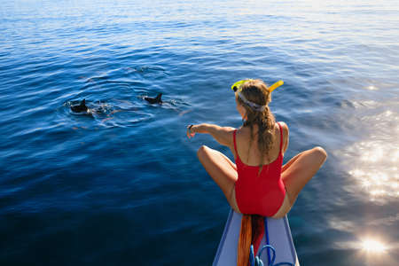 Young happy girl in snorkeling mask sit no boat. Dolphins watching adventure tour on tropical islands. Water activity, active children lifestyle, summer vacation travel with kids at family resort.