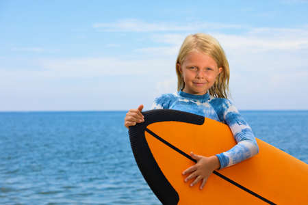 Happy baby girl - young surfer learn to ride on surfboard with fun on sea waves. Active family lifestyle, kids outdoor water sport lessons, swimming activity in surf camp. Summer vacation with child.