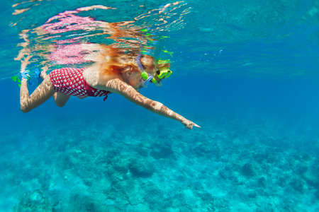Young mother with child in snorkeling mask dive in coral reef sea lagoon to explore underwater world. Family travel lifestyle in summer adventure camp. Swimming activities on beach vacation with kids.
