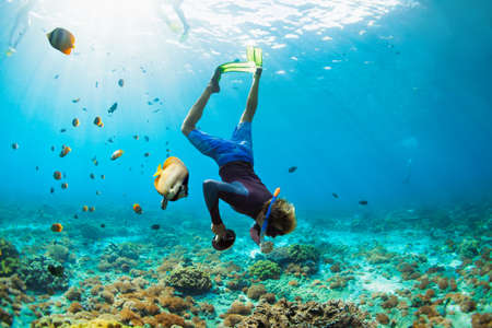 Happy family vacation. Man in snorkeling mask with camera dive underwater with tropical fishes in coral reef sea pool. Travel lifestyle, water sport outdoor adventure, swimming on summer beach holiday. Banque d'images