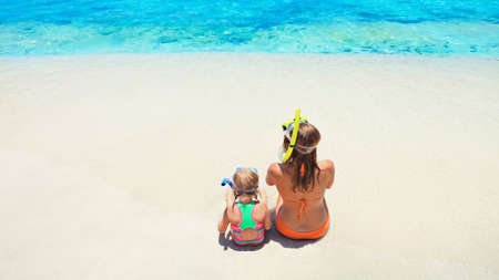 Happy family - mother, baby girl in snorkeling mask sit on white sand beach of tropical island. Look at scenic sea lagoon view. Travel adventure, swimming activity on summer holiday cruise with kids.